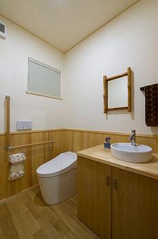 落ち着いた木調の空間にまとめた1階のトイレ