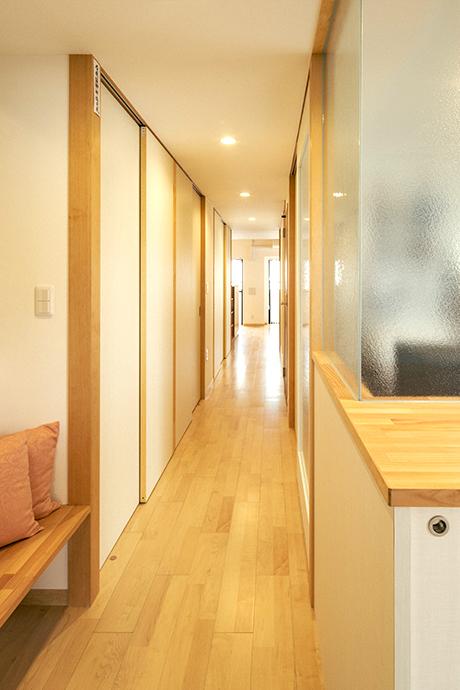 玄関からLDKに延びる中廊下。両側の部屋との間にガラスを配し、明るさと視覚的なつながりを確保。