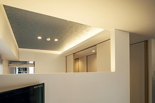 青いクロスと間接照明を組み合わせた寝室天井まわり。間接照明部分の高さは隣接する中廊下にそのまま連続する。